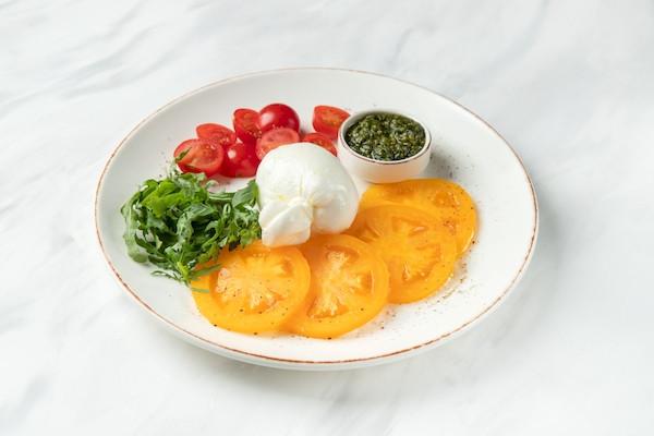 Салат Капрезе з моцарелою Бурата, двома видами томатів та соусом песто