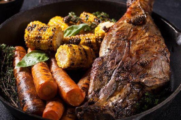 Нога ягняти запечена в вугіллі з овочами