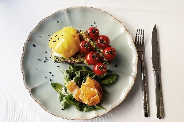 Брускета з яйцем пашот, пюре із авокадо, жовтими та червоними томатами чері